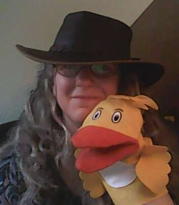 Image of the author wearing a hat and a duck glove puppet.